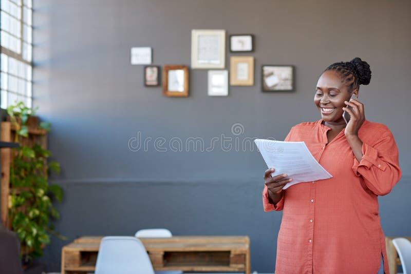 Glimlachende Afrikaanse onderneemster die op een cellphone en het lezen van administratie spreken royalty-vrije stock afbeelding