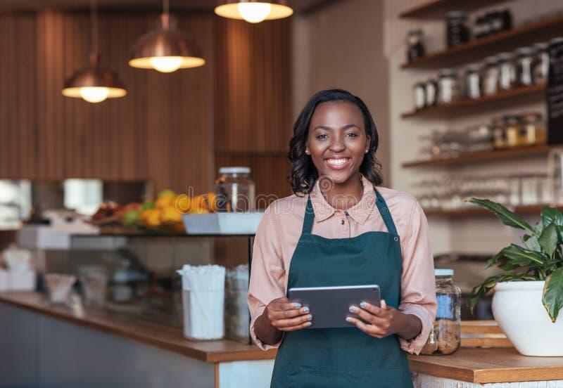 Glimlachende Afrikaanse ondernemer die een digitale tablet in haar koffie gebruiken stock fotografie