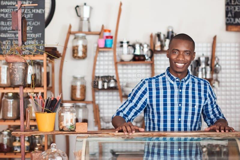 Glimlachende Afrikaanse ondernemer die zich achter de teller van zijn koffie bevinden stock fotografie