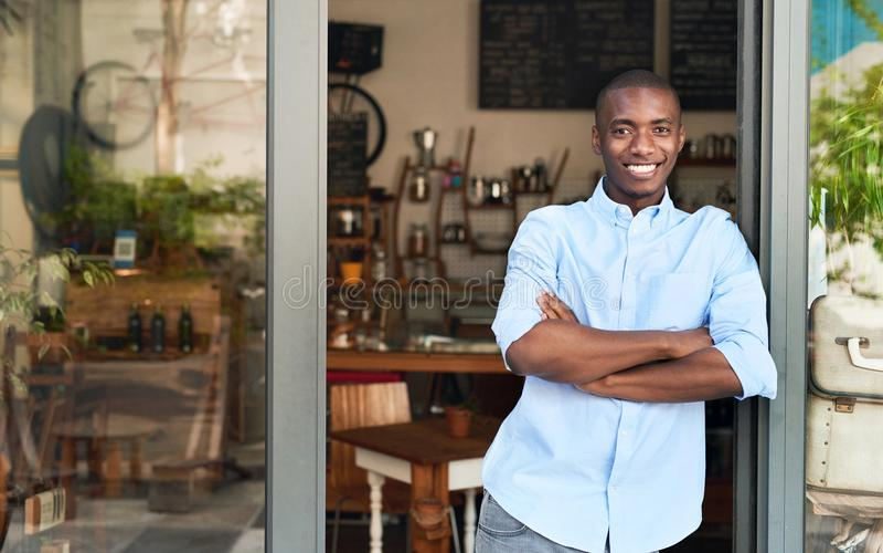 Glimlachende Afrikaanse ondernemer die zich bij de deur van zijn koffie bevinden stock foto's