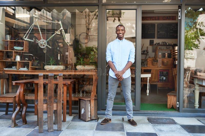 Glimlachende Afrikaanse ondernemer die zich welcomingly voor zijn koffie bevinden stock afbeelding