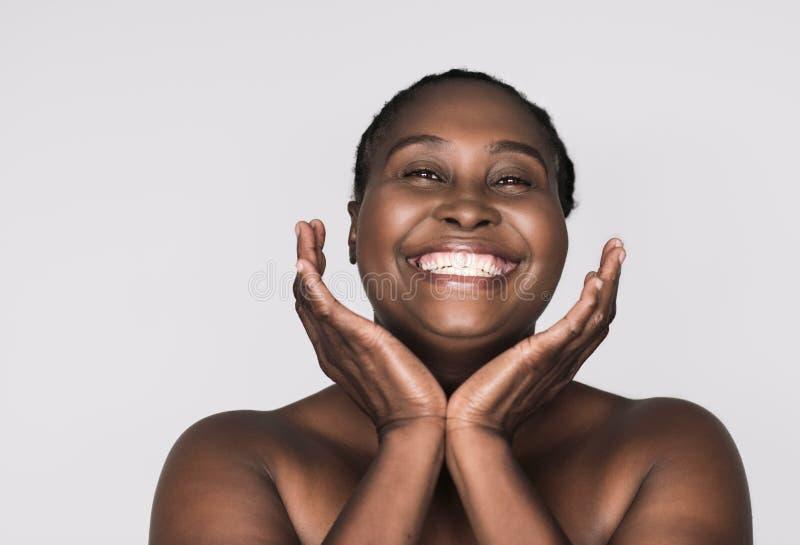 Glimlachende Afrikaanse vrouw met perfecte huid tegen een grijze achtergrond royalty-vrije stock fotografie