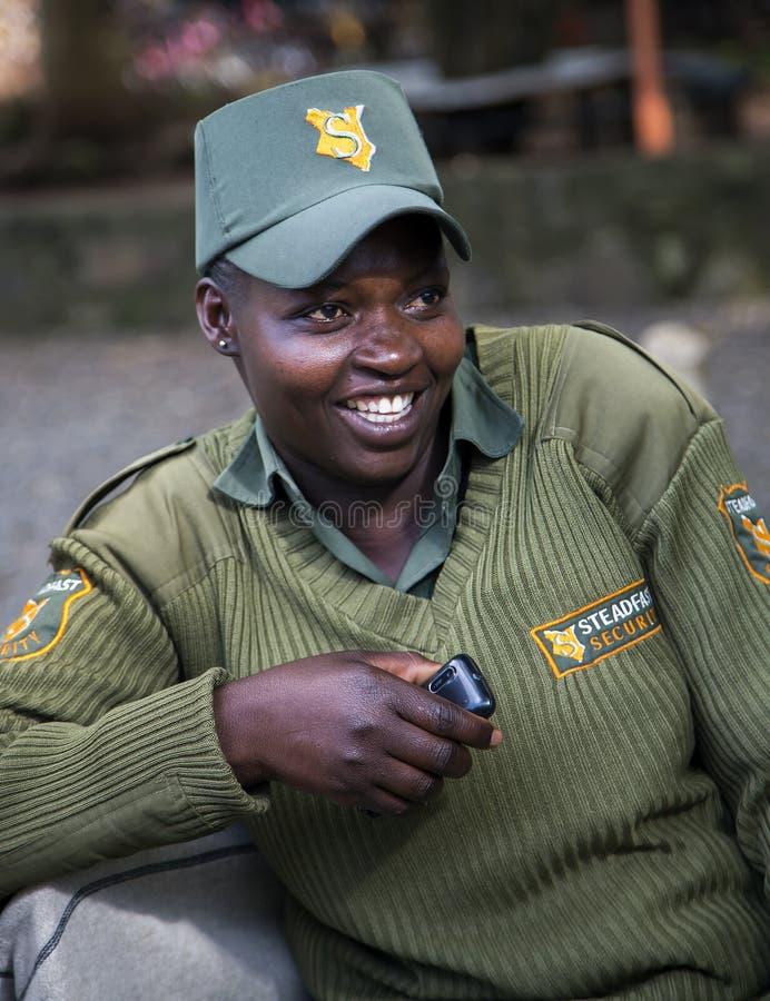 Glimlachende Afrikaanse vrouwelijke wacht in een uniform op het Girafcentrum royalty-vrije stock fotografie