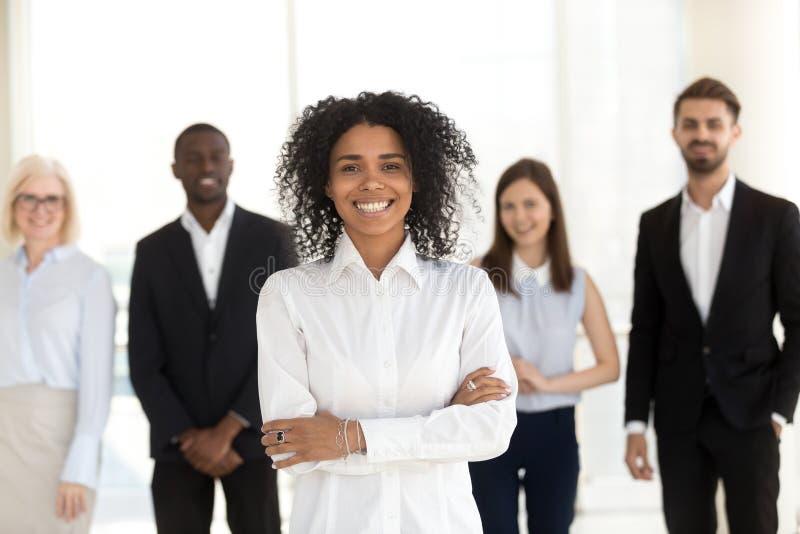 Glimlachende Afrikaanse werknemer die zich met divers team in bureau, p bevinden royalty-vrije stock fotografie