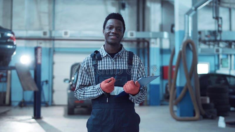 Glimlachende Afrikaanse werktuigkundige die een baanblad uitschrijven stock afbeeldingen
