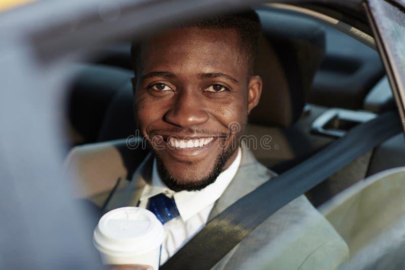 Glimlachende Afrikaanse Zakenman in Auto stock afbeelding