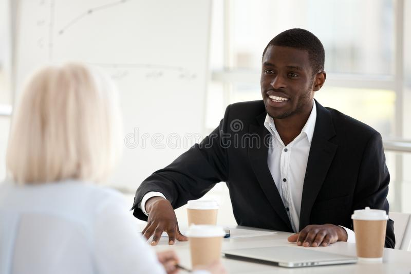 Glimlachende Afrikaanse zakenman die in kostuum aan collega bij mee spreken stock afbeeldingen