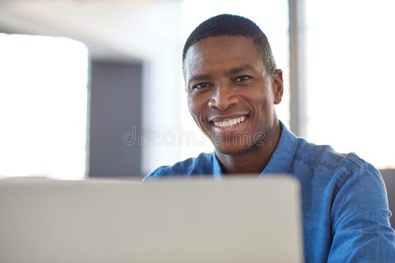 Glimlachende Afrikaanse zakenman die laptop in een bureau met behulp van royalty-vrije stock afbeelding