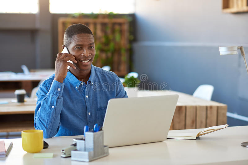 Glimlachende Afrikaanse zakenman hard bij het werk in een modern bureau stock afbeelding