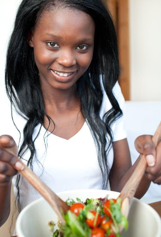 Glimlachende Afro-Amerikaanse vrouw die een salade voorbereidt royalty-vrije stock afbeelding