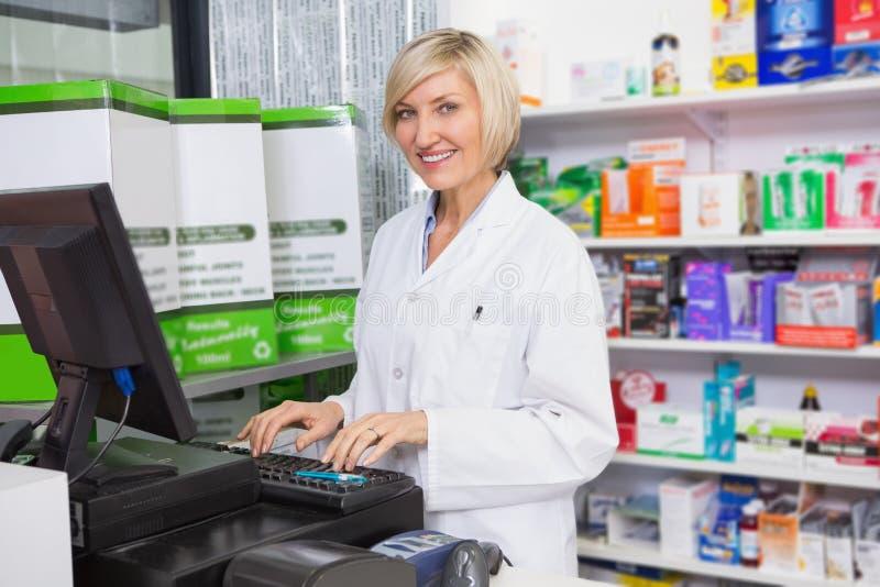 Glimlachende apotheker die computer met behulp van stock afbeeldingen