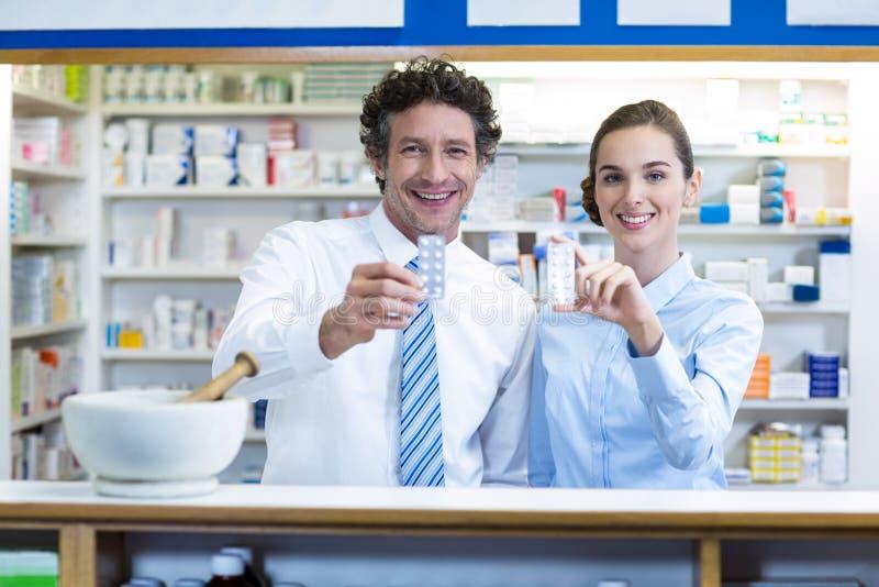 Glimlachende apotheker die geneeskunde in apotheek tonen royalty-vrije stock foto