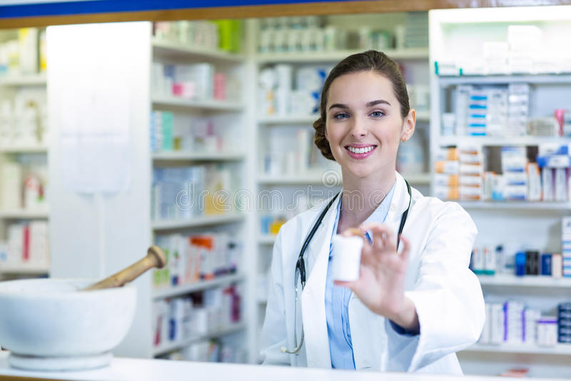 Glimlachende apotheker die geneeskundecontainer in apotheek tonen royalty-vrije stock fotografie