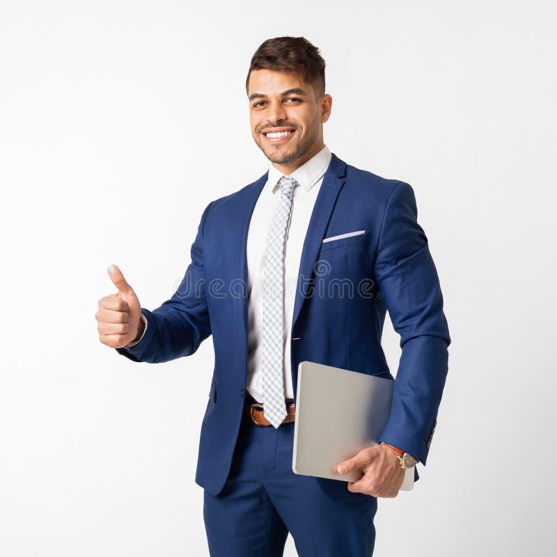 Glimlachende Arabische Zakenman Holding Tablet And die Duim tonen stock fotografie