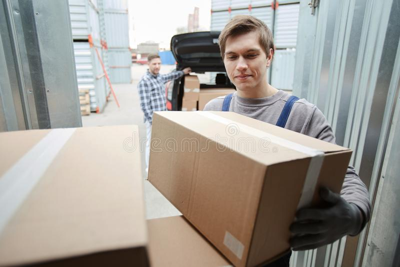 Glimlachende arbeiders bijwonende cliënt aan ladingsauto royalty-vrije stock fotografie