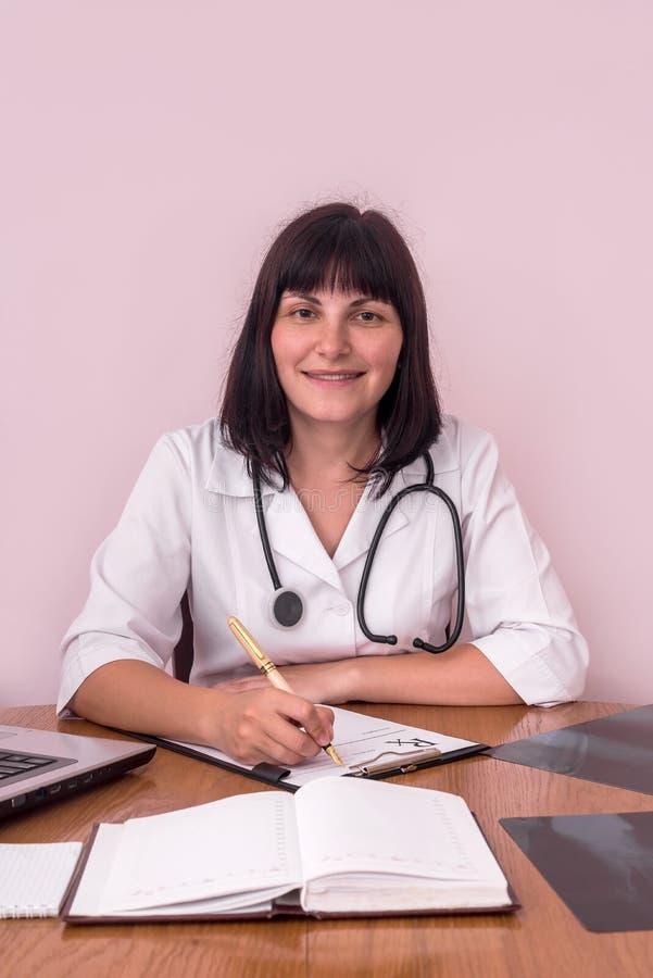 Glimlachende arts bij werkplaats met de röntgenstralen van de patiënt stock afbeeldingen