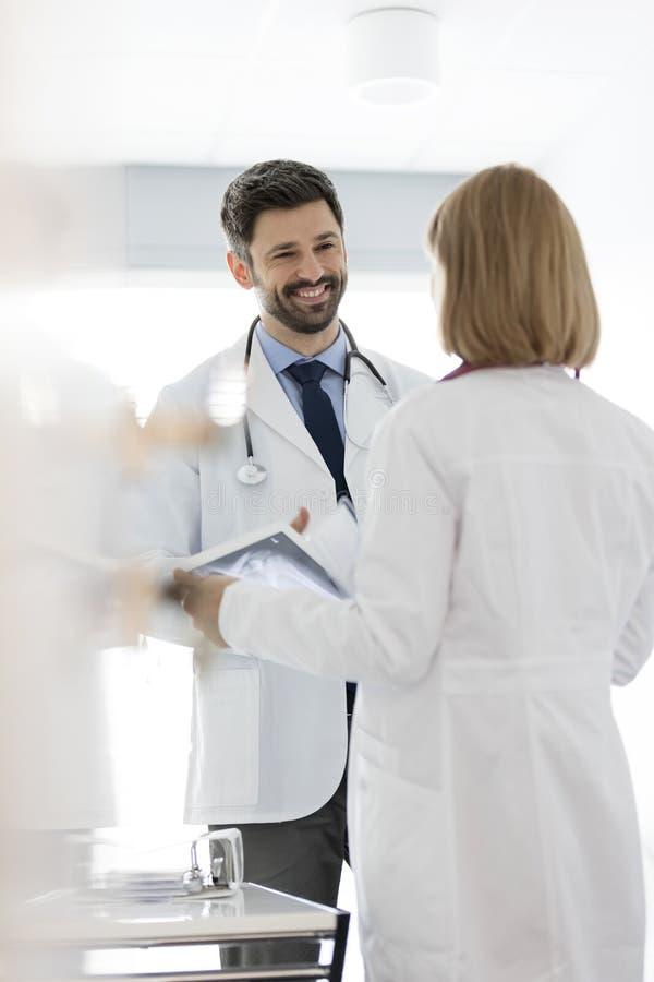 Glimlachende arts die aan collega met röntgenstraal op digitale tablet bij het ziekenhuis luisteren royalty-vrije stock foto's