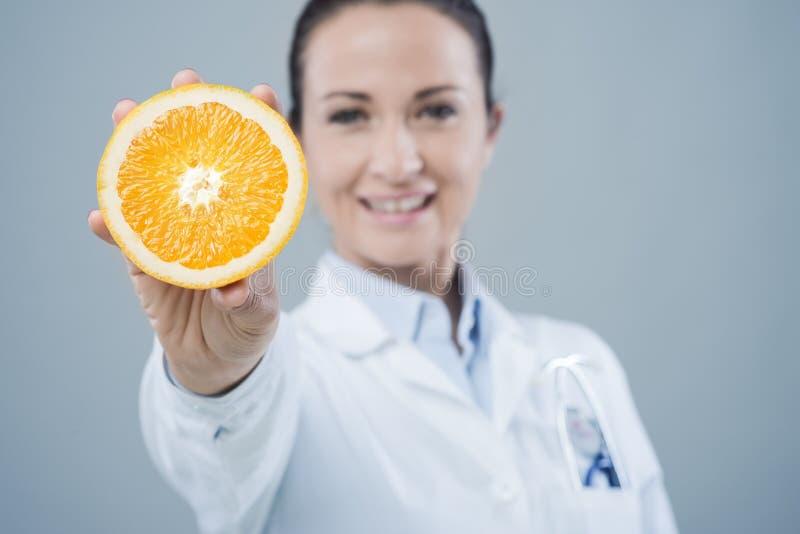 Glimlachende arts die een sappige sinaasappel tonen royalty-vrije stock foto's