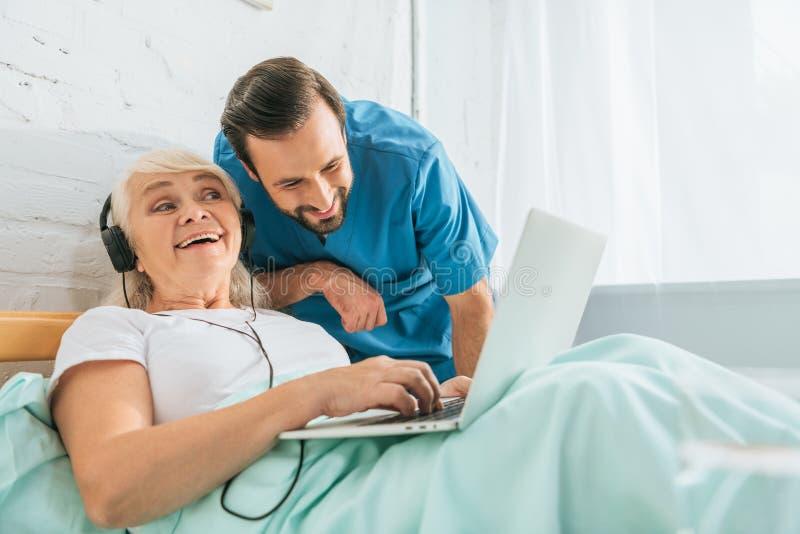 glimlachende arts die gelukkige hogere vrouw bekijken royalty-vrije stock fotografie