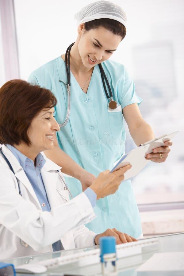 Glimlachende arts die met verpleegster werkt stock afbeelding
