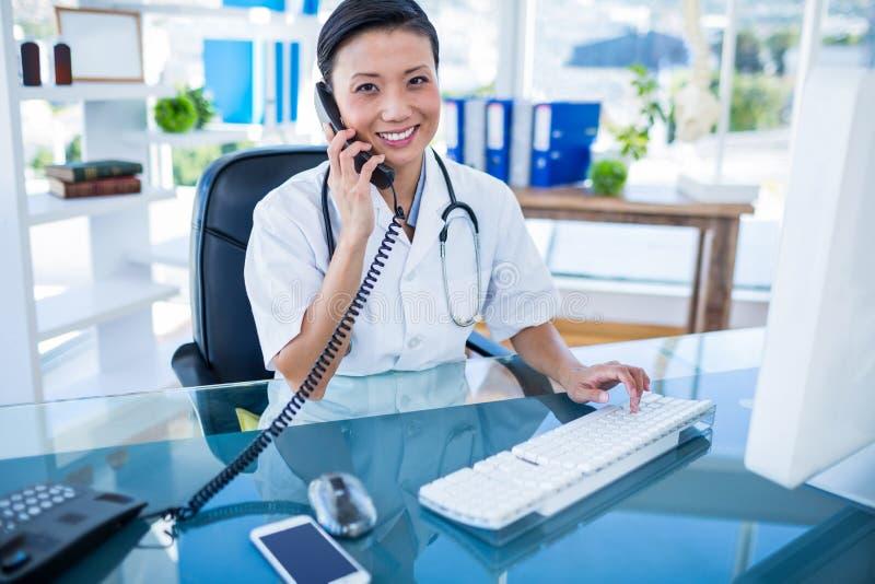 Glimlachende arts die telefoongesprek en het gebruiken van haar computer hebben stock afbeelding