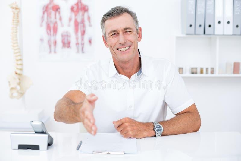Glimlachende arts die zijn hand aanbieden stock afbeelding