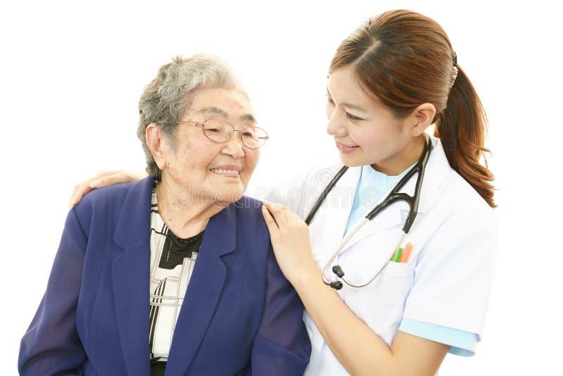 Glimlachende arts en hogere vrouw stock foto