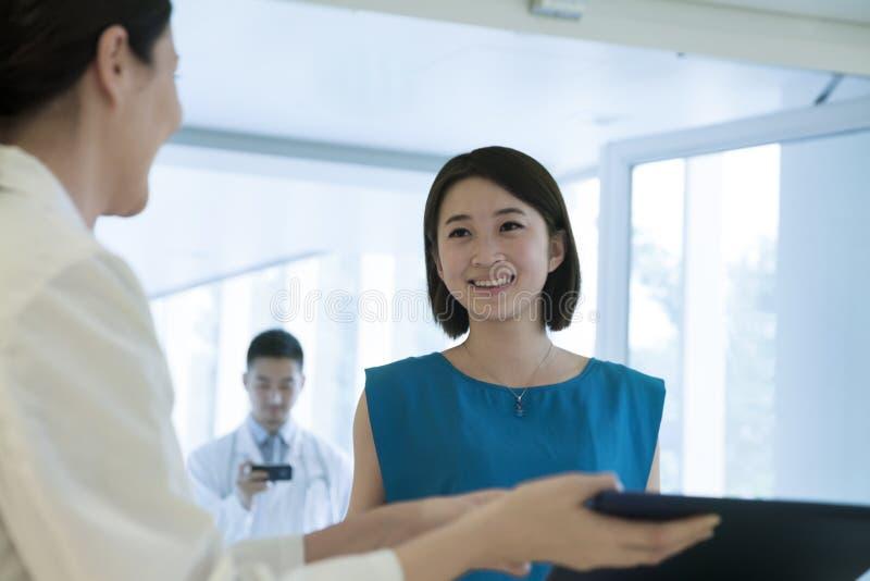Glimlachende arts en patiënt die zich door de teller in het ziekenhuis bevinden die neer medisch dossier bekijken stock afbeeldingen