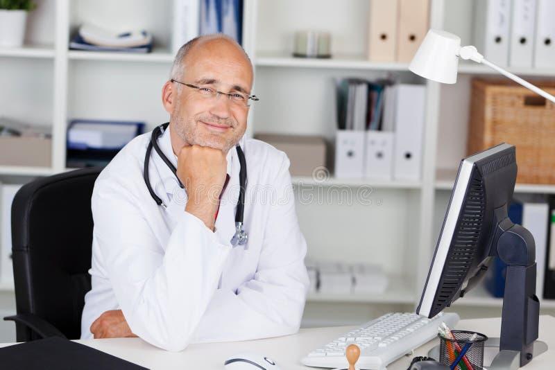 Glimlachende arts met kin op hand royalty-vrije stock afbeelding
