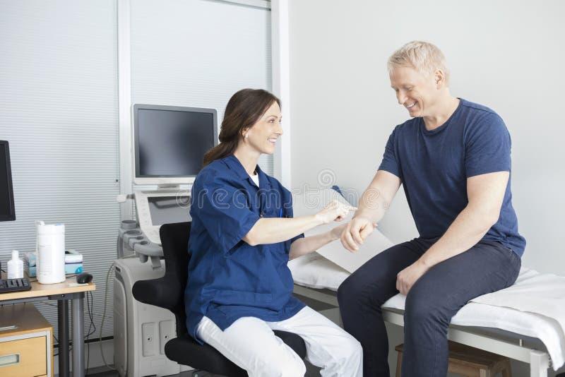 Glimlachende Arts Touching Male Patient & x27; s dient Kliniek in stock afbeelding
