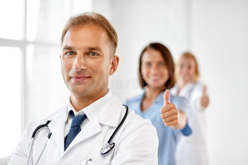 Glimlachende arts in witte laag bij het ziekenhuis stock foto's