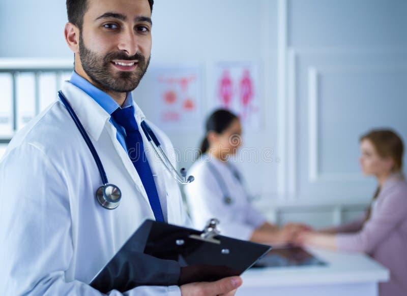 Glimlachende artsenmens die zich voor zijn team en patiënt bevinden royalty-vrije stock afbeelding