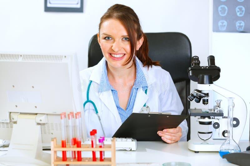 Glimlachende artsenvrouw die in bureau werkt royalty-vrije stock foto