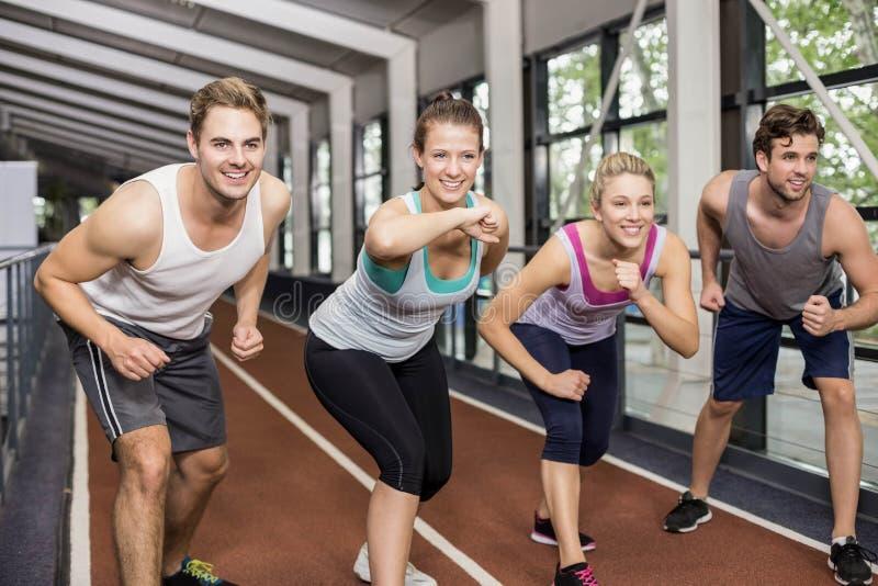 Glimlachende atletische vrienden die gaan beginnen te lopen stock foto's