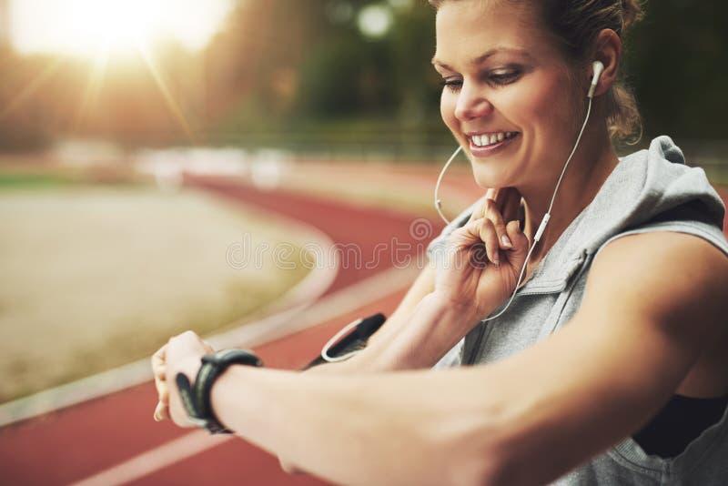 Glimlachende atletische vrouw die haar horloge en het voelen van de impuls op spoorgebied bekijken stock fotografie