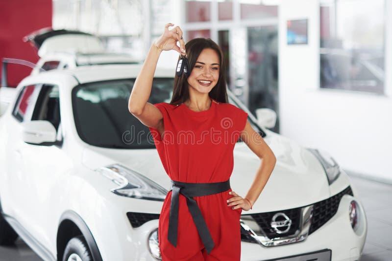 Glimlachende autoverkoper die uw nieuw autosleutels, handel drijven en verkoopconcept overhandigen Gelukkig meisje de koper royalty-vrije stock foto