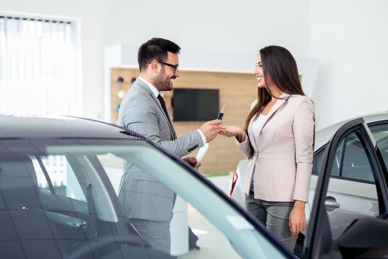 Glimlachende autoverkoper die uw nieuwe autosleutels overhandigen Gelukkig meisje de koper royalty-vrije stock afbeelding