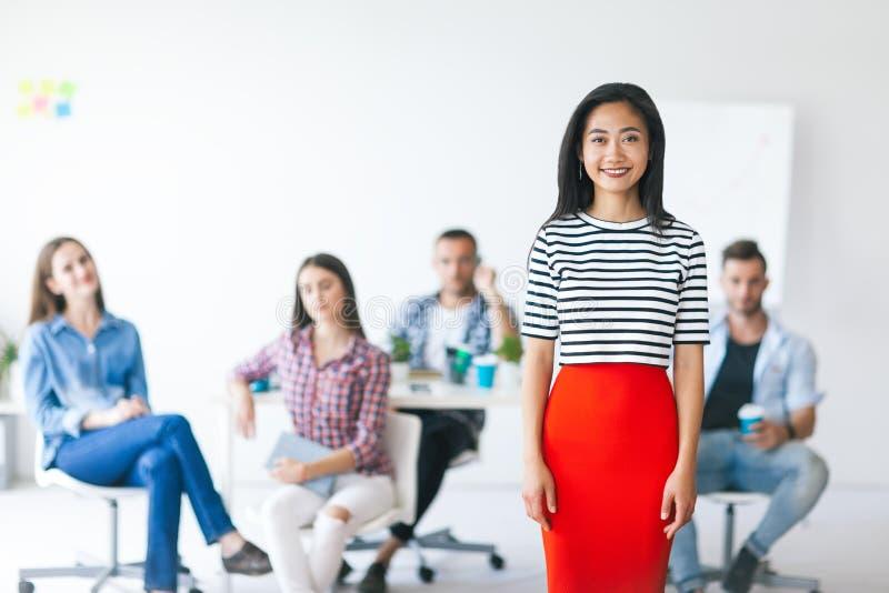 Glimlachende Aziatische bedrijfsleider met haar team op achtergrond royalty-vrije stock foto