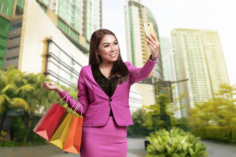 Glimlachende Aziatische bedrijfsvrouw selfie met holding het winkelen zakken stock afbeeldingen