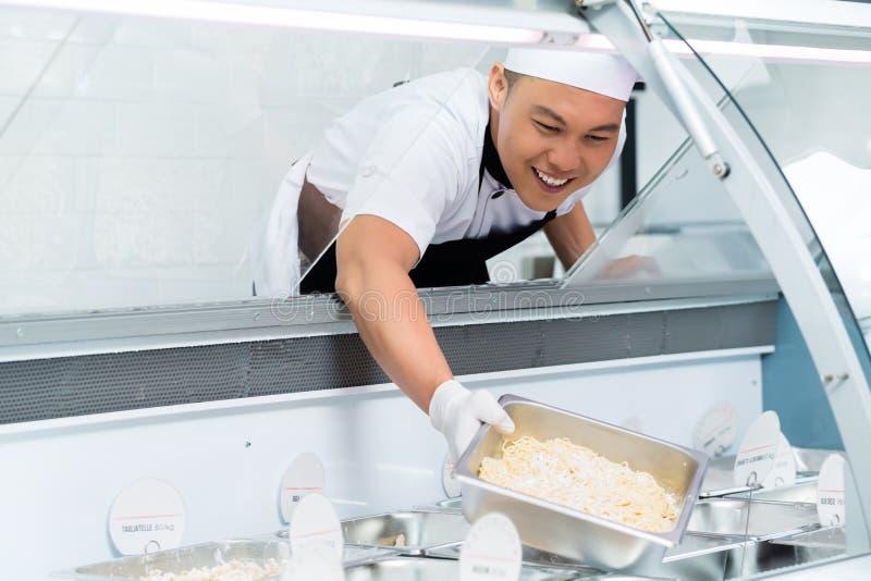 Glimlachende Aziatische chef-kok die een vertoningsteller vullen stock fotografie