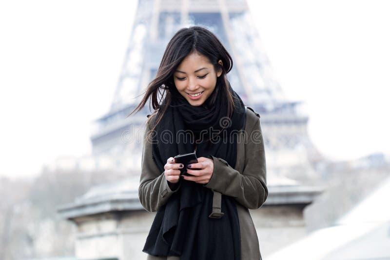 Glimlachende Aziatische jonge vrouw die haar mobiele telefoon voor de toren van Eiffel met behulp van stock afbeelding