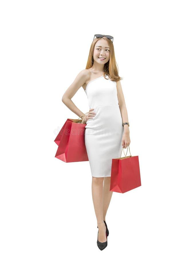 Glimlachende Aziatische luxevrouw die zich met rode document zakken bevinden royalty-vrije stock foto's