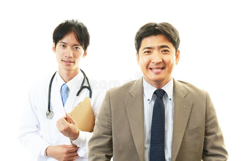 Glimlachende Aziatische medische arts en patiënt stock foto