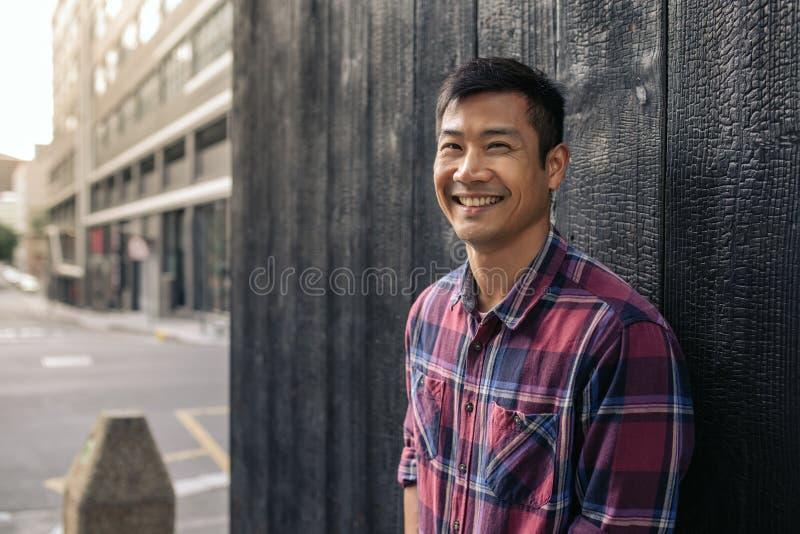 Glimlachende Aziatische mens die tegen een muur in de stad leunen royalty-vrije stock foto's