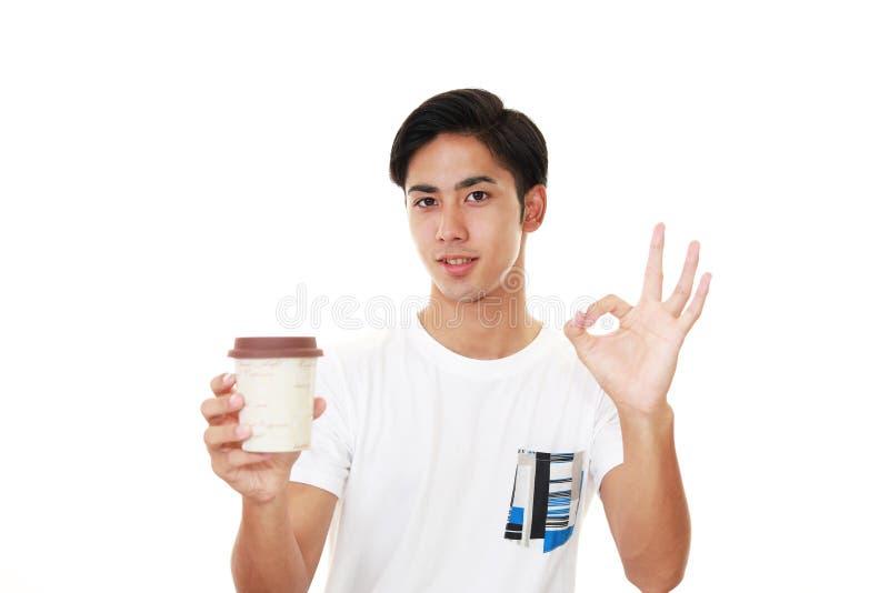 Glimlachende Aziatische mens het drinken koffie royalty-vrije stock afbeeldingen
