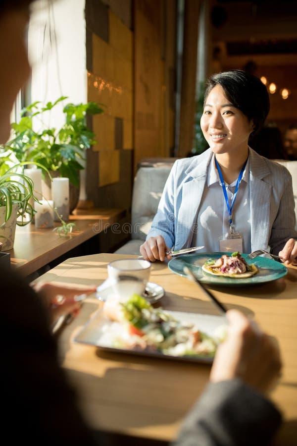 Glimlachende Aziatische onderneemster die lunch met vriend hebben stock foto