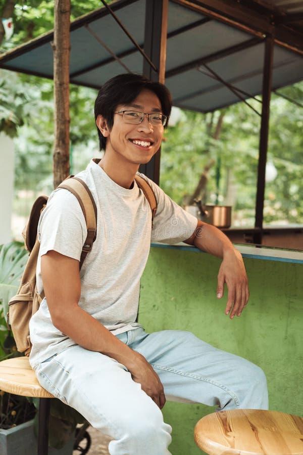 Glimlachende Aziatische studentenmens die rugzak dragen stock afbeelding