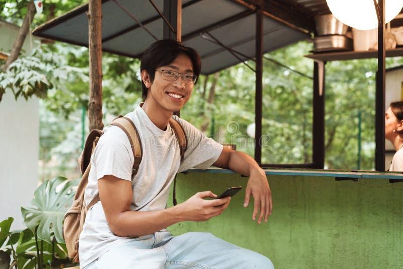 Glimlachende Aziatische studentenmens die rugzak dragen stock fotografie