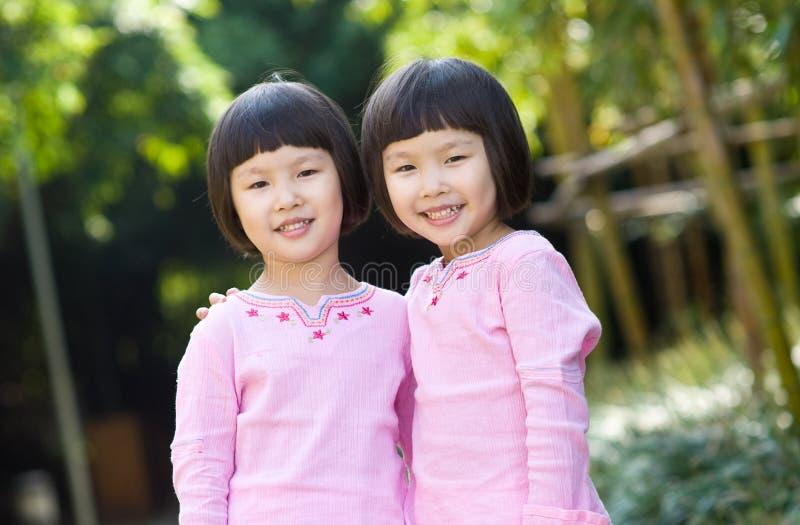 Glimlachende Aziatische tweelingmeisjes royalty-vrije stock afbeeldingen
