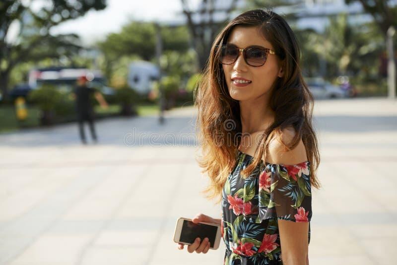 Glimlachende Aziatische vrouw die met smartphone camera bekijken stock afbeelding